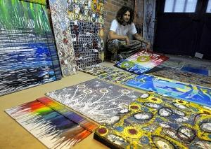 Artist Michael Michaud lays out his work in the second stall of his garage workshop in Enfield. By year's end he will have created 365 pieces of art. Some will be donated and some will be used to provide $3,650 for a needy artist. Michaud, who goes by the name MiJuMi, says that like Bob Marley, he wants to use his art to contribute to others. (Jim Michaud/Journal Inquirer)