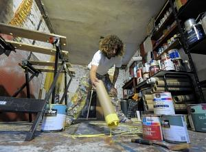 Artist Michael Michaud of Enfield uses a large cardboard tube as one of his painting tools.(Jim Michaud/Journal Inquirer)
