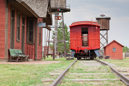 A vintage red wooden caboose sits at a old western train station as part of a historical display.